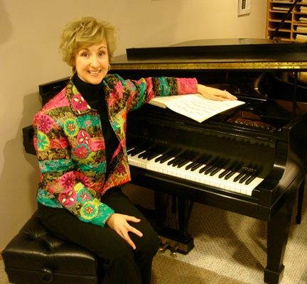 Jacqueline Ryz seated at one of the two Steinway grand pianos in her studio