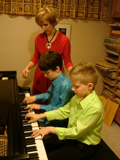 Jacqueline coaching two young boys in a piano duet