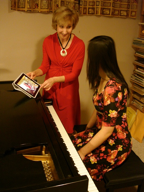 Jacqueline using an iPad to show a student a video